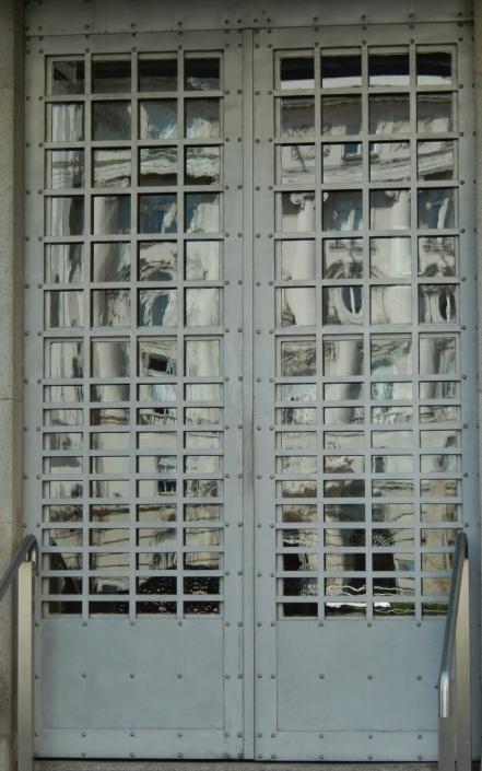 Otto Wagner Postsparkasseneingangstür-Detail; Foto schnuppe von gwinner - in den Fenstern spiegelt sich das mächtige, in historisierendem Stil gebaute (bis 1913) Regierungsgebäude gegenüber.